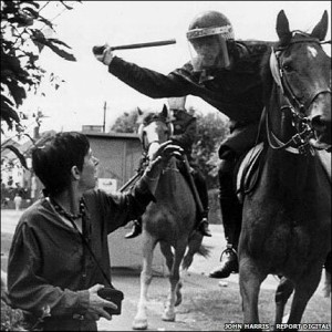 Офицер конной полиции замахнулся для удара  дубинкой по голове Лесли Болтон - женщины с фотоаппаратом в руках, которая выступала против закрытия шахт. (http://news.bbc.co.uk/local/sheffield/hi/people_and_places/history/newsid_8217000/8217946.stm)